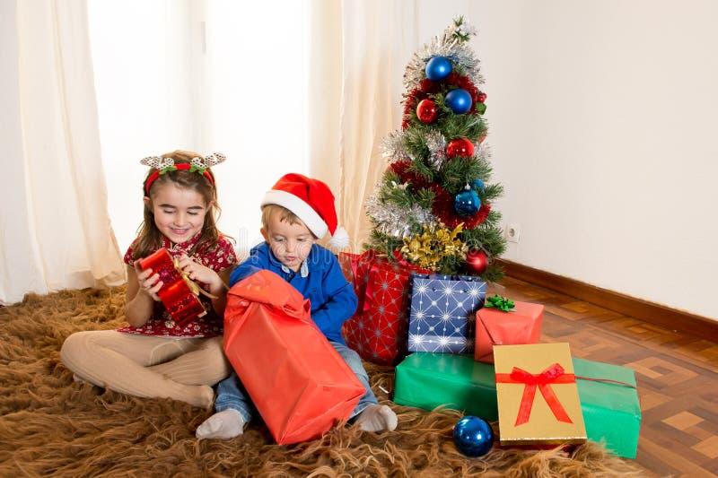 地毯开头圣诞节礼物的小孩 免版税库存图片