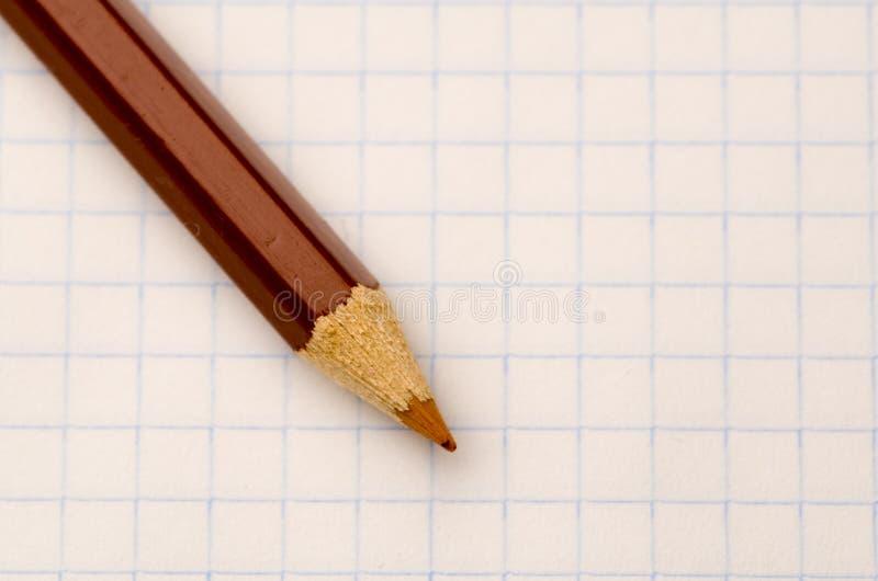 地点在笔记本板料的被削尖的铅笔 图库摄影