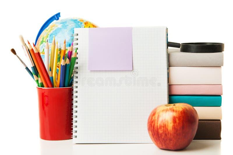 地球、被隔绝的笔记本堆和铅笔 免版税库存图片