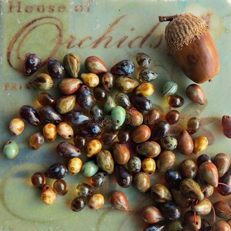 地球口气在五颜六色的背景的玻璃珠泪珠 秋天首饰做和工艺的被启发的小珠混合 库存例证