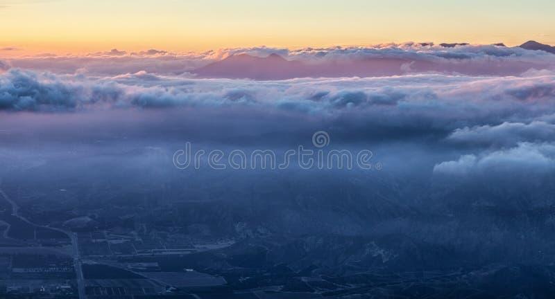 地球和天堂惊人视图:在蓝色云彩和金黄和桃红色天空下的夜城市 图库摄影
