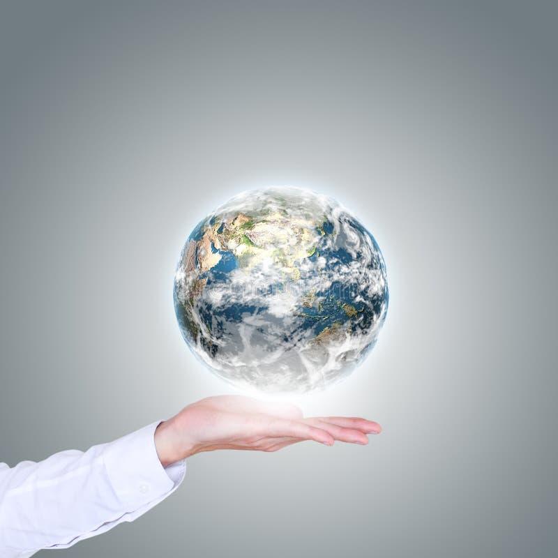 地球在人的手上漂浮 免版税库存照片