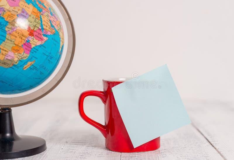 地球地图世界地球咖啡杯稠粘的笔记说谎的减速火箭的葡萄酒土气老桌背景的正面图关闭 库存照片