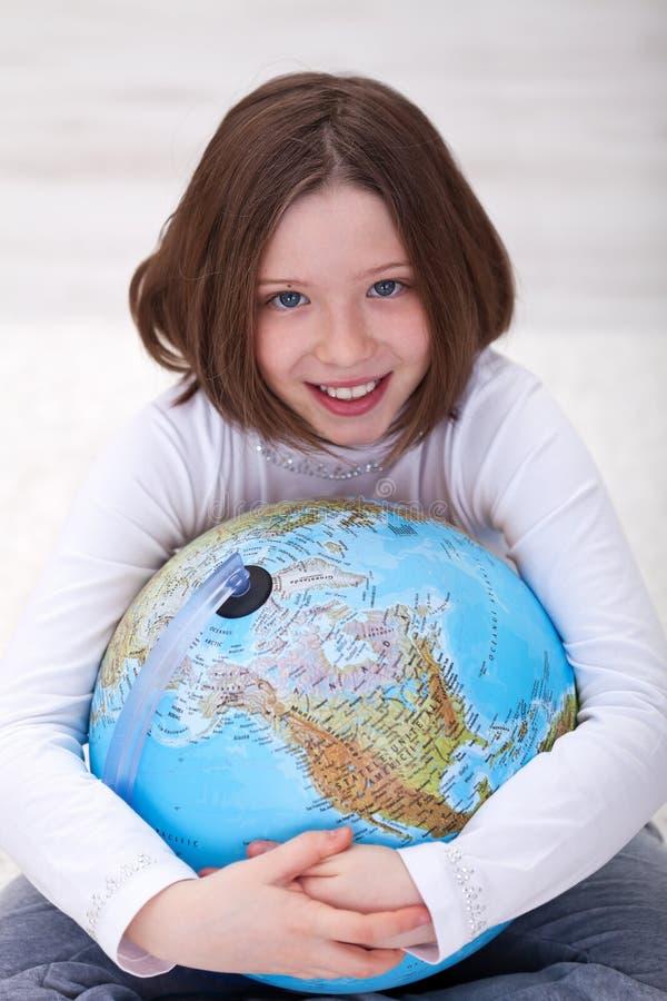 地球拥抱年轻人的女孩地球 免版税图库摄影