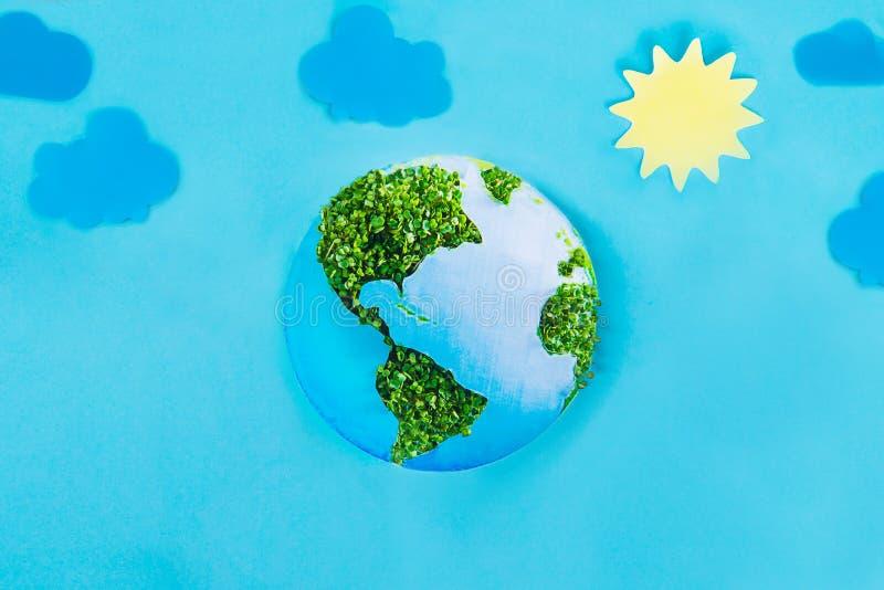 地球模型由纸和新绿色制成发芽在蓝色背景的拼贴画与纸太阳和云彩 绿色行星创造性浓缩 免版税库存照片