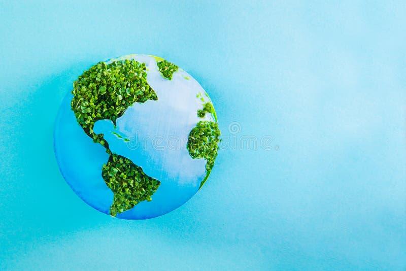 地球模型由纸和新绿色制成发芽在蓝色背景的拼贴画 绿色行星创造性的概念 变褐环境叶子去去的绿色拥抱本质说明说法口号文本结构树的包括的日地球 有选择性 免版税图库摄影