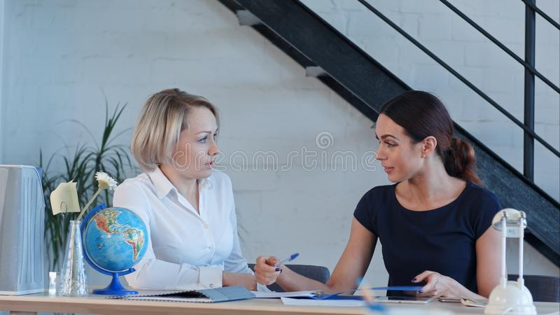 地理的两位老师谈话在类以后 免版税图库摄影