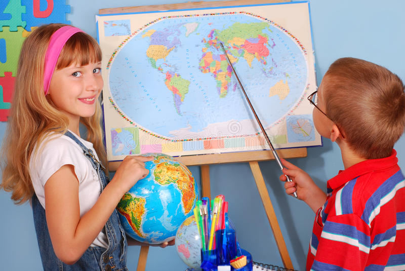 地理课程的女小学生和男小学生 免版税库存图片