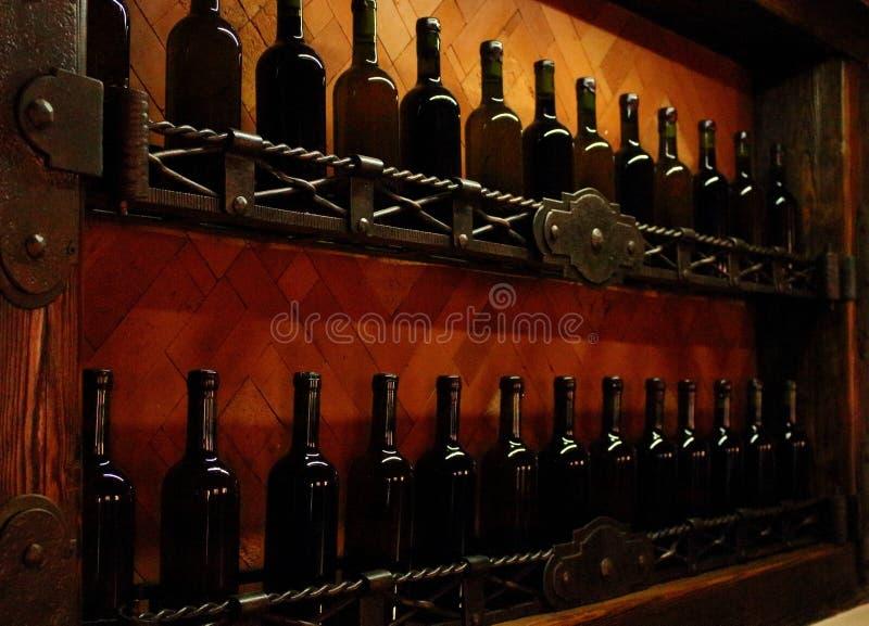 地窖搁置与黑暗的被塞住的酒瓶对浅褐色的木墙壁 免版税库存照片