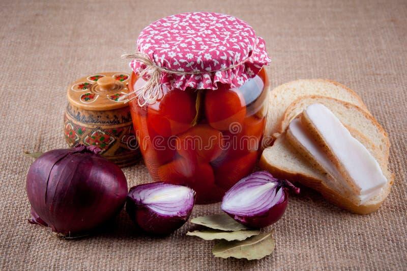 地道乌克兰静物画 在瓶子的蕃茄,葱,面包, 库存照片