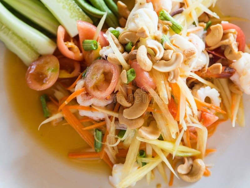 地道传统沙拉用绿色番木瓜、新鲜蔬菜和草本,在板材的海鲜在泰国餐馆 免版税库存照片