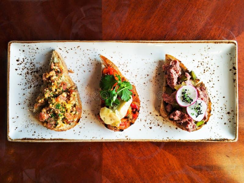 地道传统西班牙塔帕纤维布在午餐的,顶视图木桌上设置了 bruschetta的选择在有壳的面包的 库存照片