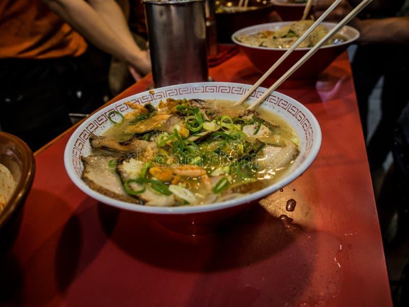 地道大阪拉面在一家拥挤的街边餐馆 免版税库存照片