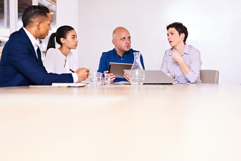 地道小组坐在会议桌上的商人 免版税库存图片