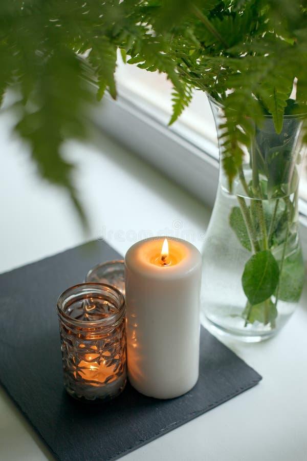 地道平静的大气 亲属Hygge缓慢的居住的样式 在烛台的蜡烛在窗台和蕨的石板材 免版税库存照片