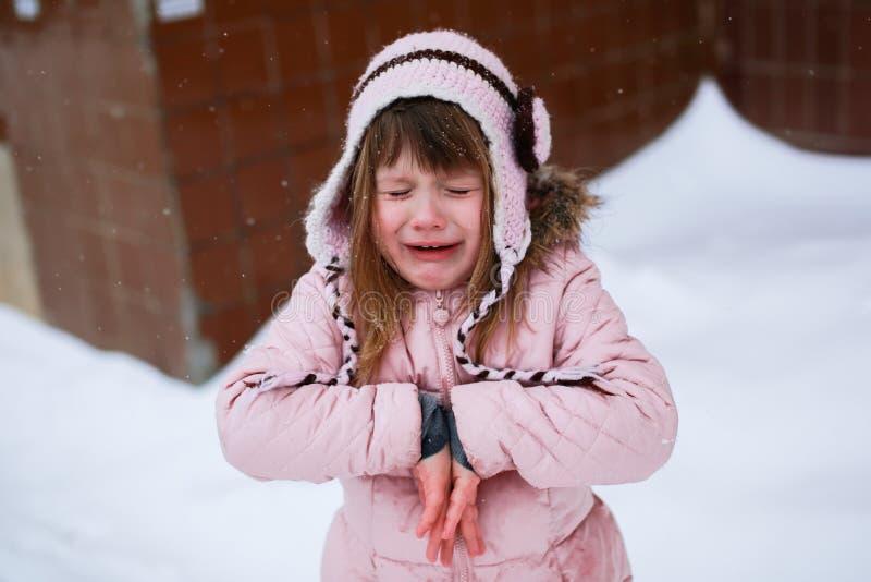 轻轻地结冰外面在冬天的桃红色夹克的哭泣的女孩 免版税图库摄影