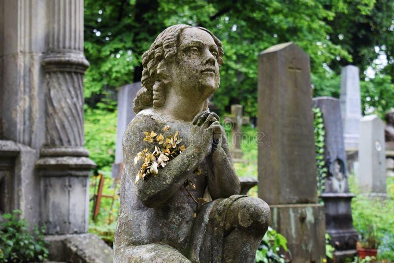 场面在公墓:下跪的女孩的雕象,祈祷 免版税库存图片