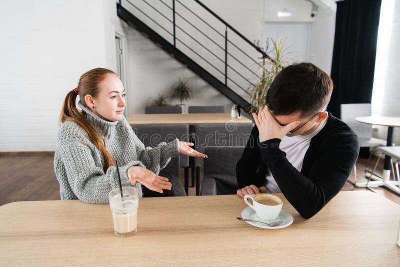 坏关系概念 男人和妇女分歧的 坐在咖啡馆的年轻夫妇有争吵,被触犯的妻子和 免版税图库摄影