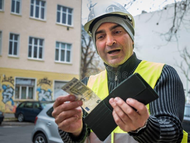 坏惊奇:建筑工人和他空的钱包 库存图片