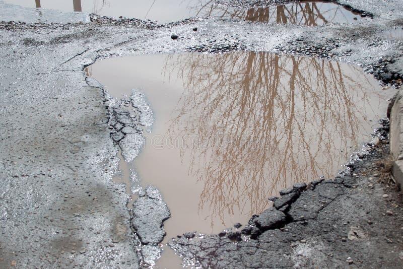 坏涂了柏油有一个大坑洼的路充满水 危险被毁坏的路基 免版税库存照片