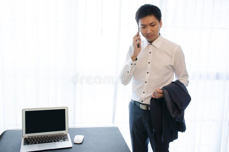 坏消息,严肃的亚洲商人身分在办公室,谈话由手机和看在与桌面的白色背景 免版税库存照片