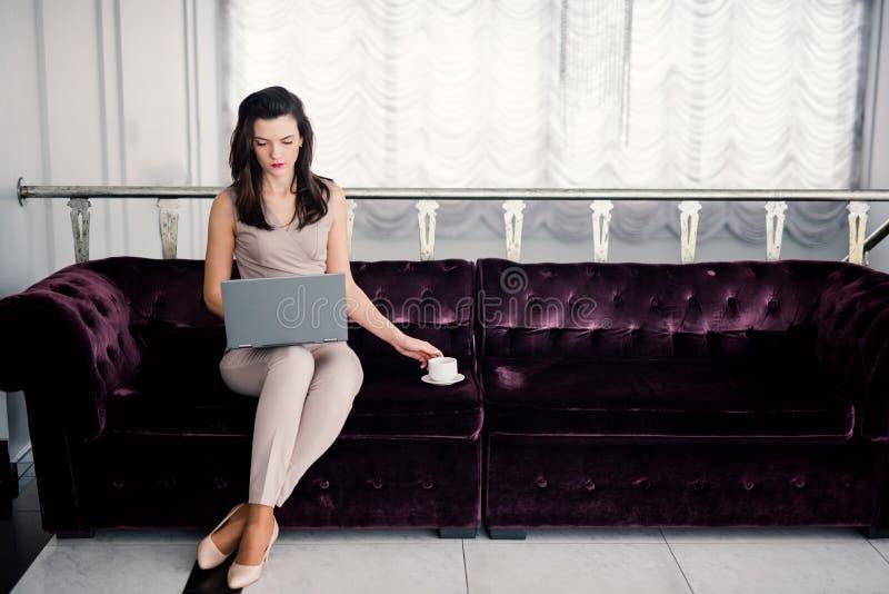E 坐一个沙发在客厅和使用膝上型计算机的成功的年轻美女,拿着coffe杯子 库存照片