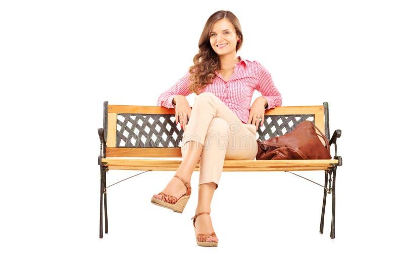坐一个长木凳和看a的美丽的深色的妇女 库存照片
