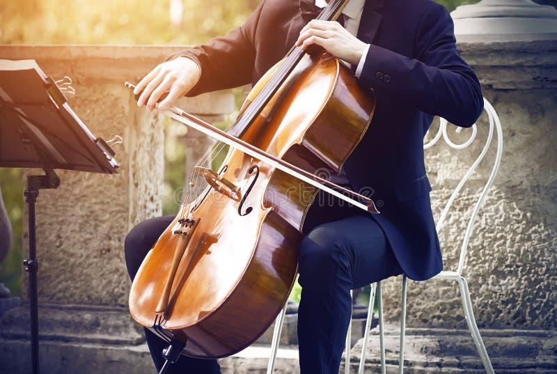 坐一把白色椅子和使用在大提琴的衣服的音乐家 库存图片