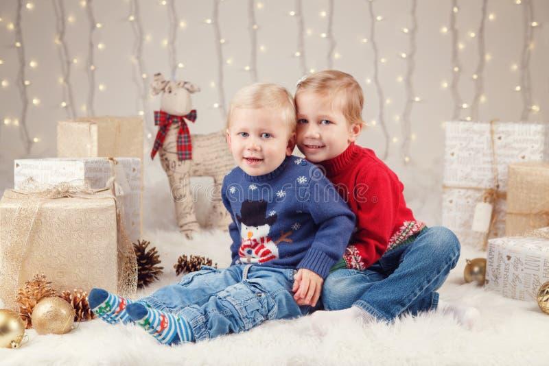 坐一起拥抱的毛线衣的白种人孩子兄弟和姐妹庆祝圣诞节或新年 库存图片