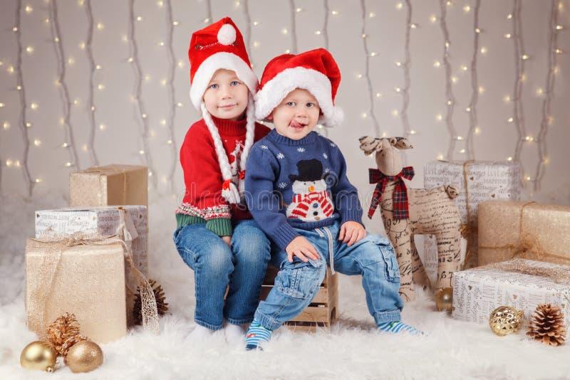 坐一起拥抱的毛线衣的白种人孩子兄弟和姐妹庆祝圣诞节或新年 免版税图库摄影