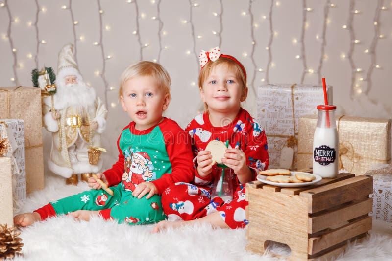坐一起拥抱的毛线衣的白种人孩子兄弟和姐妹庆祝圣诞节或新年 库存照片