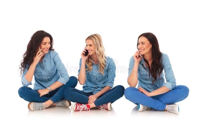 坐三名偶然的妇女和在电话里说 免版税库存图片