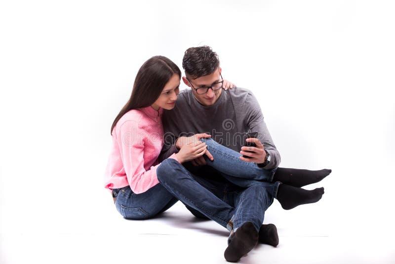 坐下和神色在电话的玻璃的年轻行家人和妇女 库存照片