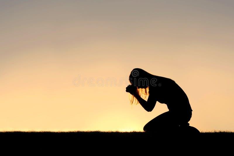 坐下在祷告剪影的基督徒妇女 免版税库存照片