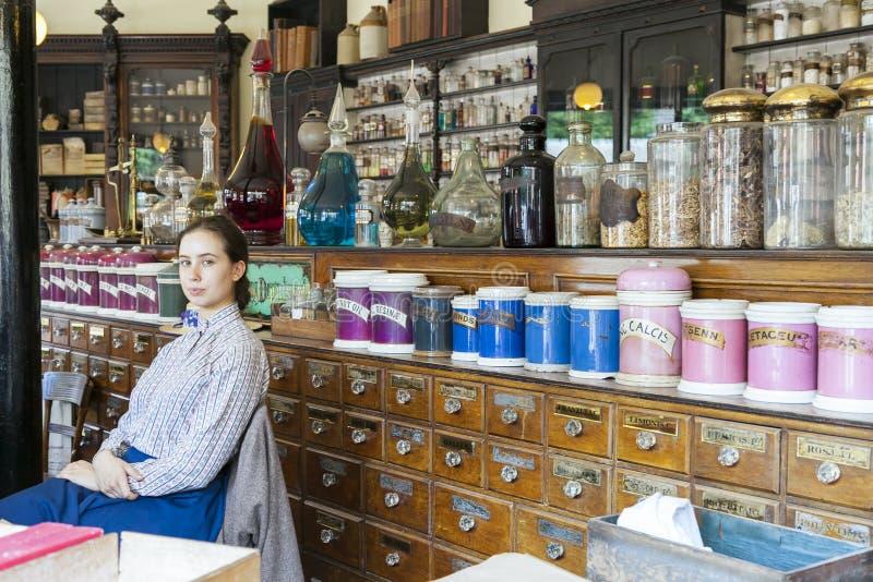 坐下在维多利亚女王时代的化学家的年轻女性销售助理 库存图片