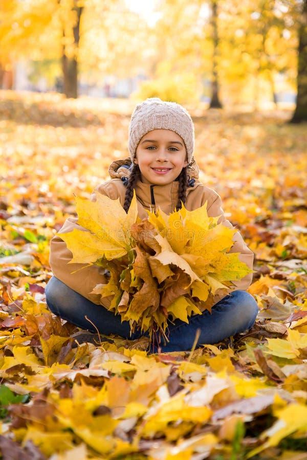 坐下落的叶子在秋天公园和拿着黄色槭树leav的花束逗人喜爱的微笑的小女孩 免版税库存图片