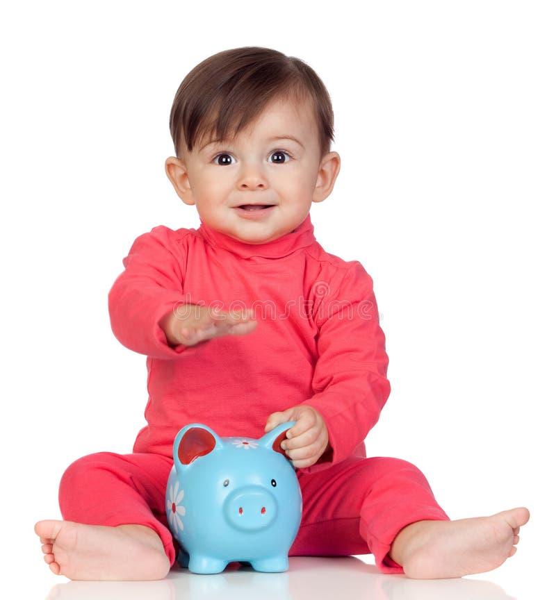 坐与一家蓝色贪心银行的可爱的女婴 免版税库存照片