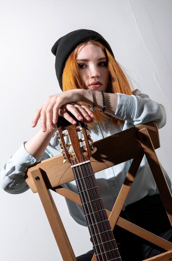 坐与一把声学吉他的女孩 免版税库存照片