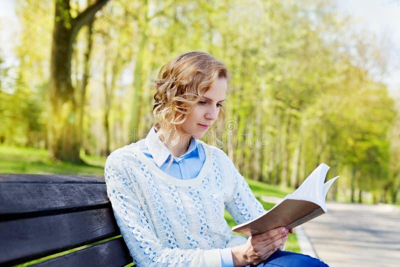 坐与一本书的衬衣的美丽的年轻学生女孩在她的手上在一个绿色公园 图库摄影
