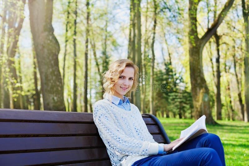 坐与一本书的衬衣的年轻学生女孩在她的手上在绿色公园、科学和教育,读 图库摄影