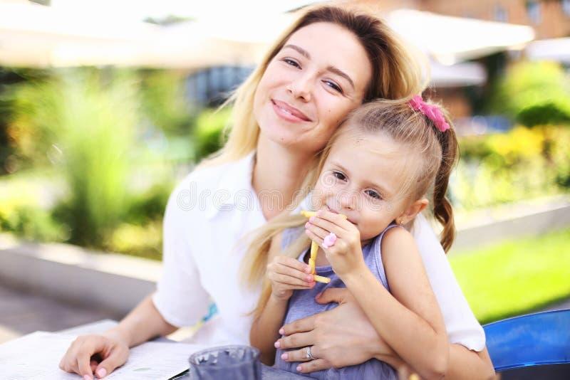坐与一点女儿的年轻母亲吃薯条在街道咖啡馆 免版税库存照片
