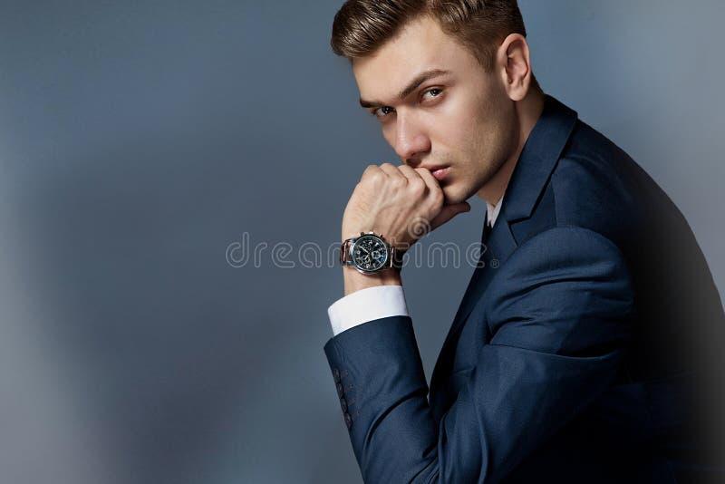 坐与与手表的一套衣服的一个人的画象,演播室 免版税库存图片
