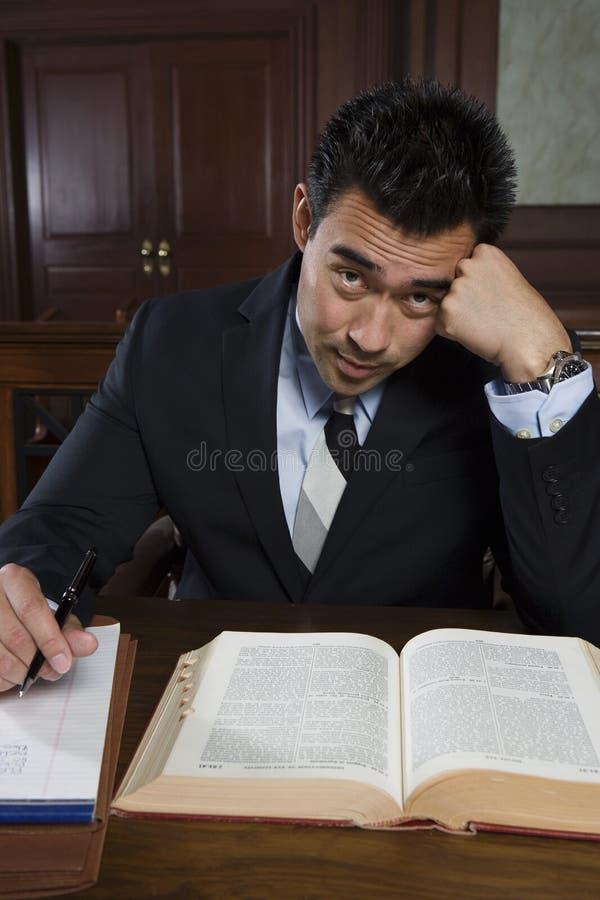 坐与书和笔记的被拉紧的提倡者 免版税库存图片