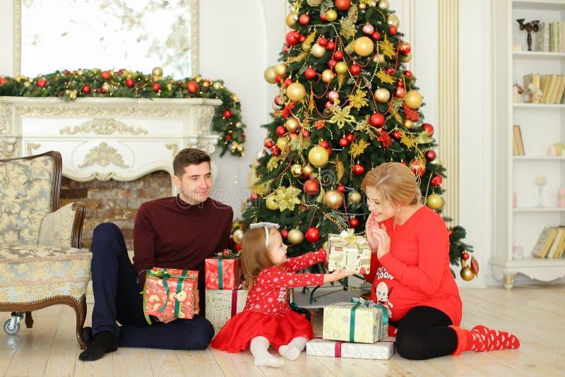 坐与人和小女儿的怀孕的白种人妇女在圣诞树和gifting的礼物附近 库存照片