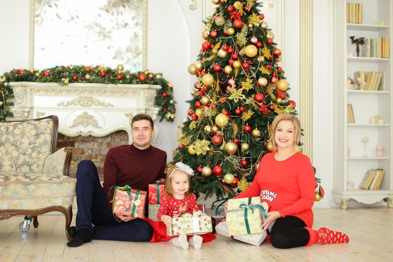 坐与人和小女儿的怀孕的白肤金发的妇女在圣诞树和gifting的礼物附近 库存图片