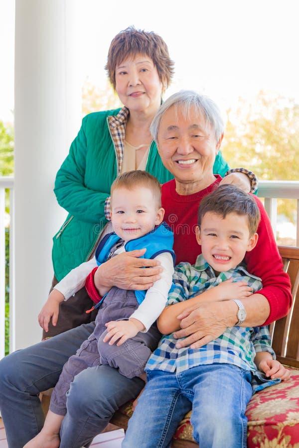 坐与他们的混合的族种Grandc的资深成人中国夫妇 免版税库存照片