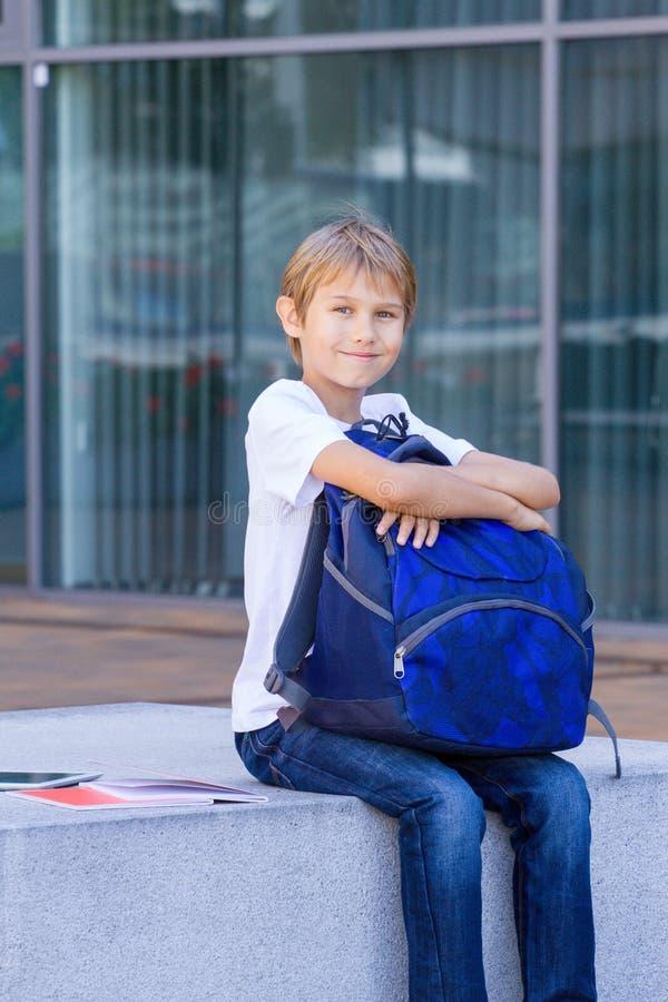 坐与他的背包、书和片剂计算机的男孩室外 库存图片