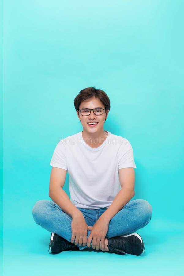 坐与他的腿的地板盘和微笑为照相机的年轻偶然亚裔人 在蓝色背景 库存照片