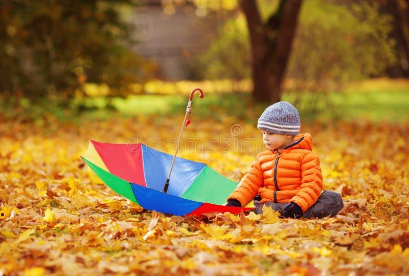坐与伞的孩子在美好的秋季天 免版税库存图片