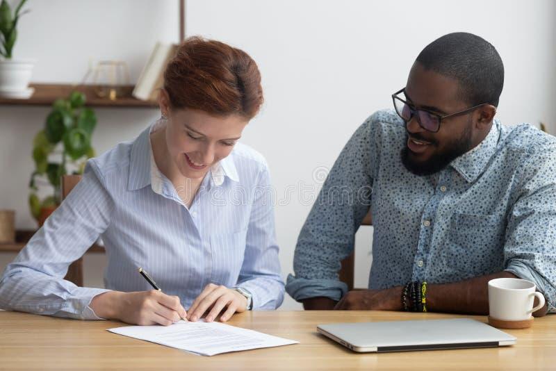 坐与公司所有者一起的女性签署的工作合同 免版税库存图片